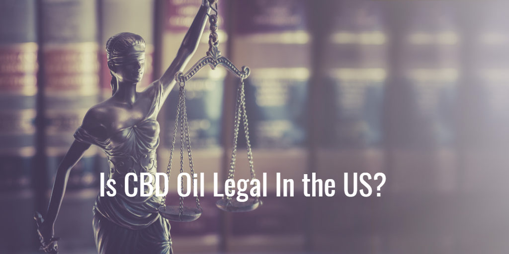 Justice Scales with law books behind it and the question is cbd oil legal in the US?