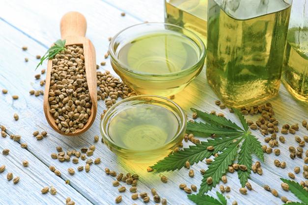 hemp oil in a glass with hemp seeds spilled around hemp seed oil jar next to hemp leaf